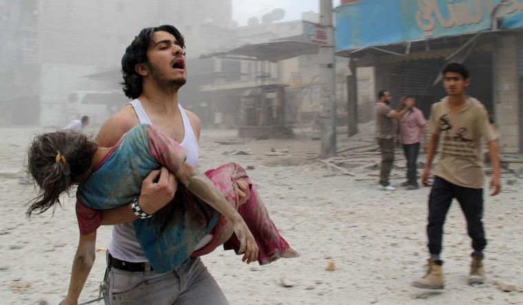 A man carries a young girl who was injured in a reported barrel-bomb attack by government forces on 3 June, 2014 in Kallaseh district in the northern city of Aleppo BARAA AL-HALABI/AFP/Getty Images